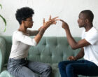 Black married couple sitting on sofa looking at each other sorting out relationships having problems in relations. Emotional boyfriend and girlfriend quarrelling gesturing feels angry and dissatisfied